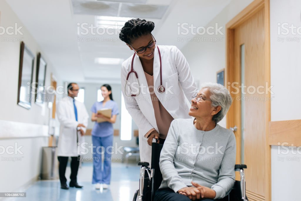 Female doctor pushing senior patient on wheelchair A female doctor pushing a senior patient on a wheelchair in a hospital, looking at each other and smiling. 20-29 Years Stock Photo