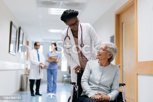 A female doctor pushing a senior patient on a wheelchair in a hospital, looking at each other and smiling.