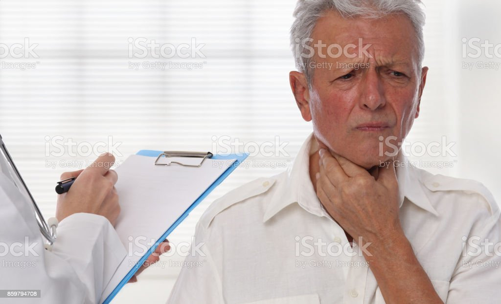 Female doctor senior man suffering from throat pain during medical exam. Man getting thyroid gland control. stock photo