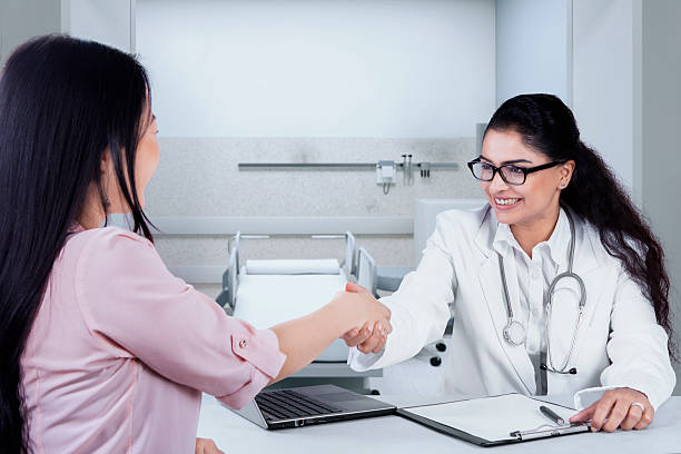 Female doctor shaking hands to patient stock photo