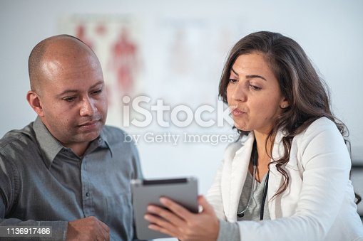 istock Female Doctor Shares Test Results with Patient Using Digital Tablet 1136917466