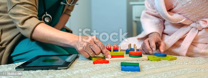 istock Female doctor showing geometric shapes to elderly patient 1176484198