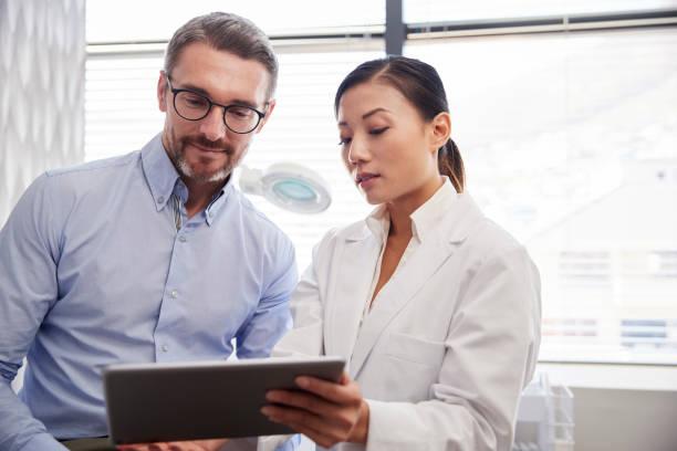 doctor femenino mostrando resultados de la prueba de paciente masculino maduro en la tableta digital en la oficina - dermatología fotografías e imágenes de stock