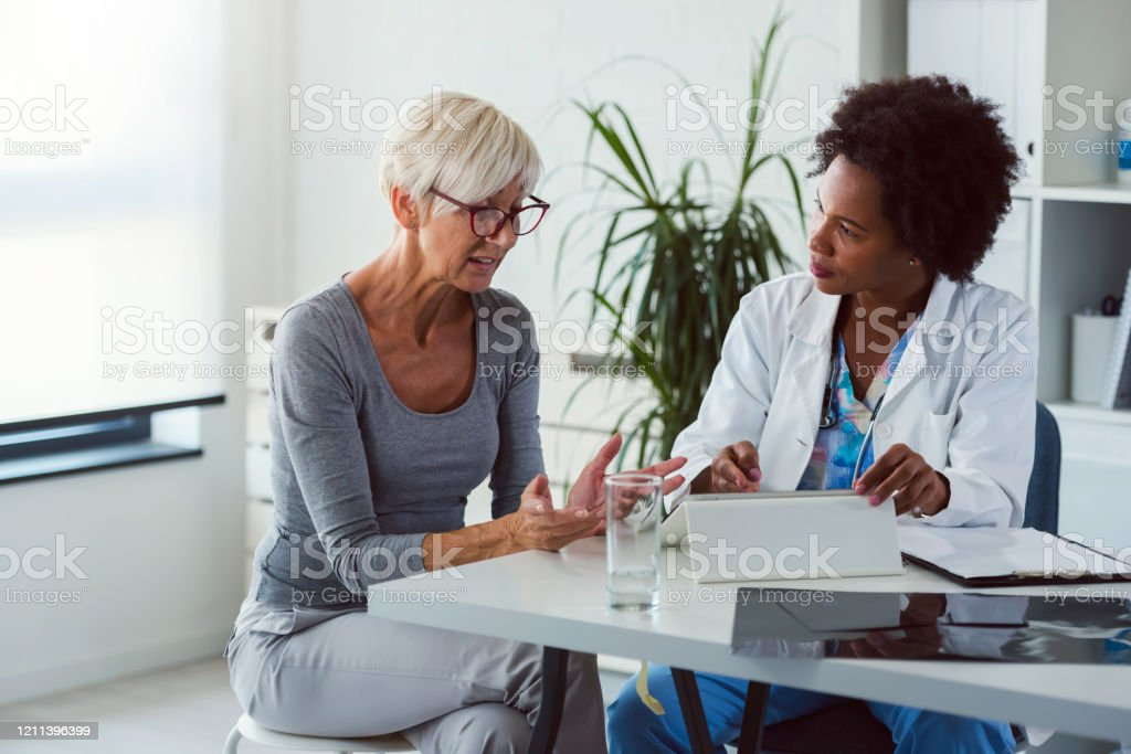 A female doctor sits at her desk and chats to an elderly female patient while looking at her  test results A female doctor sits at her desk and chats to an elderly female patient while looking at her  test results Adult Stock Photo
