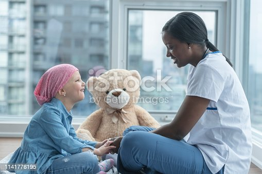 istock Female doctor sits with child patient fighting cancer 1141776195