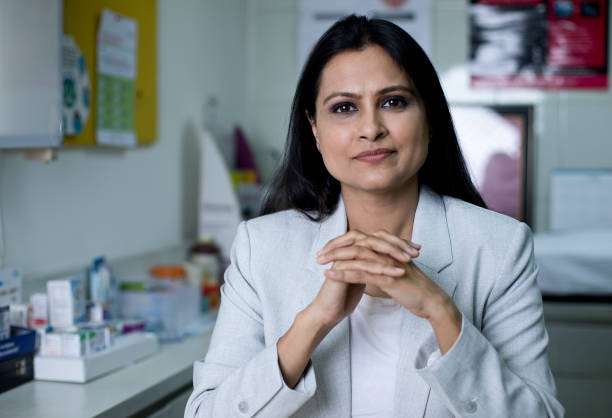 Female doctor sitting at desk in office clinic stock photo