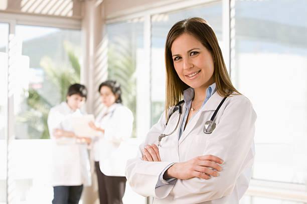Mujer médico sonriente con los brazos cruzados - foto de stock