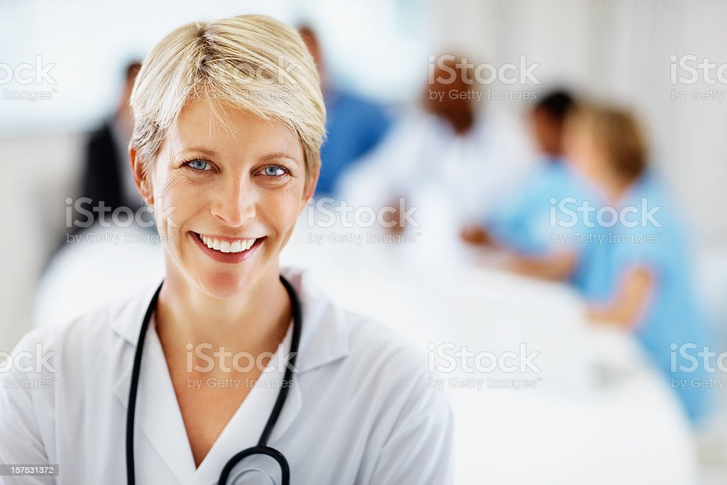 Female doctor smiling with colleagues at the back stock photo