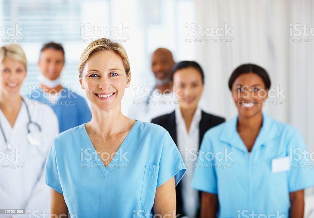 Ärztin lächelnd mit Kollegen im Hintergrund – Foto
