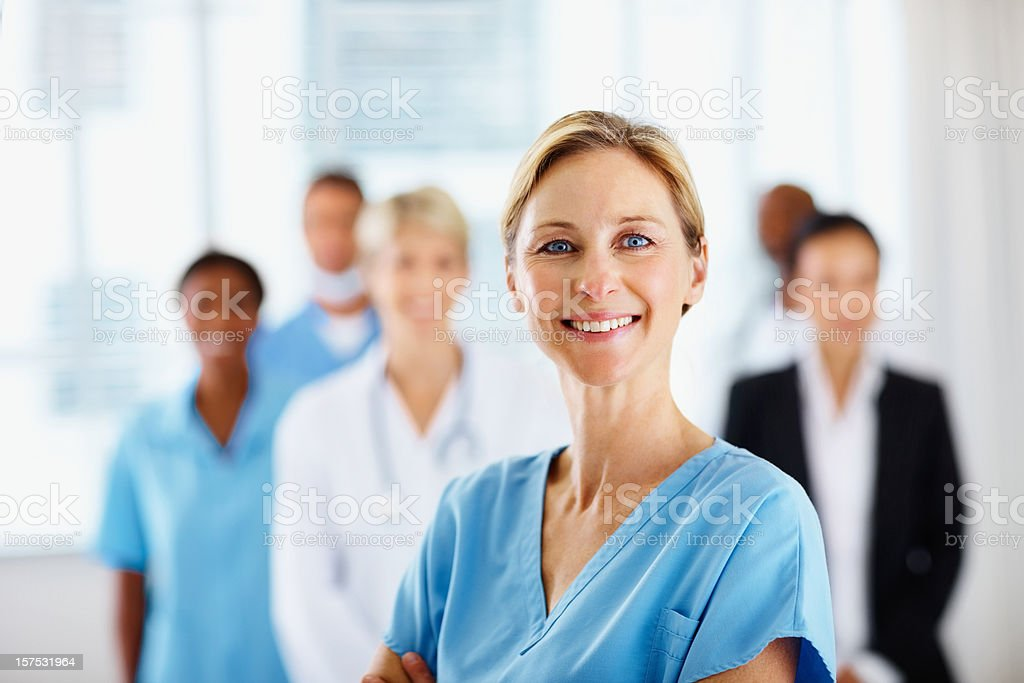 Female doctor smiling with colleagues in the background stock photo