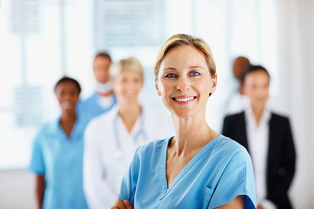 female doctor smiling with colleagues in the background - female nurse stock photos and pictures