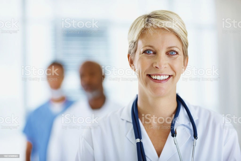 Female doctor smiling with colleagues in the background royalty-free stock photo