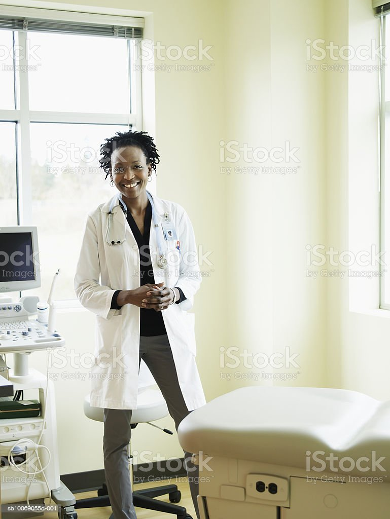 Female doctor standing in exam room, smiling, portrait 免版稅 stock photo