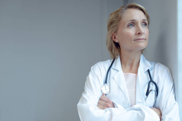 Female doctor standing with arms crossed in the hospital stock photo