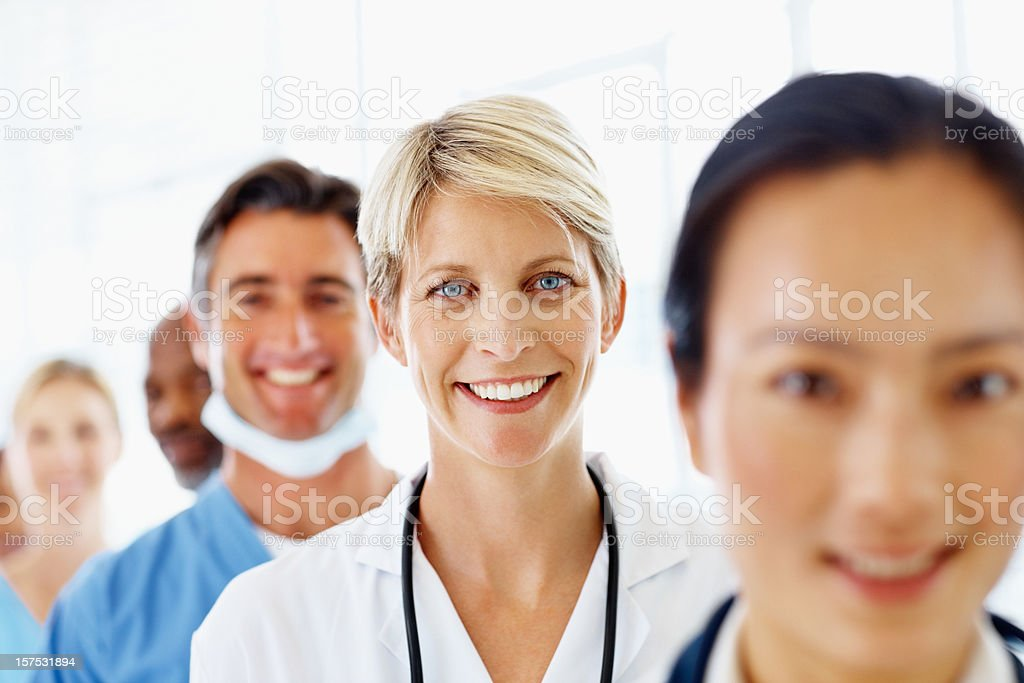 Female doctor standing with her staff and smiling royalty-free stock photo