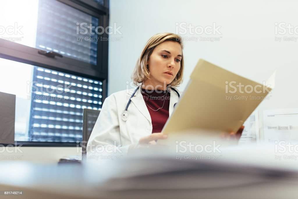 Female doctor sitting in her office and studying medical records....