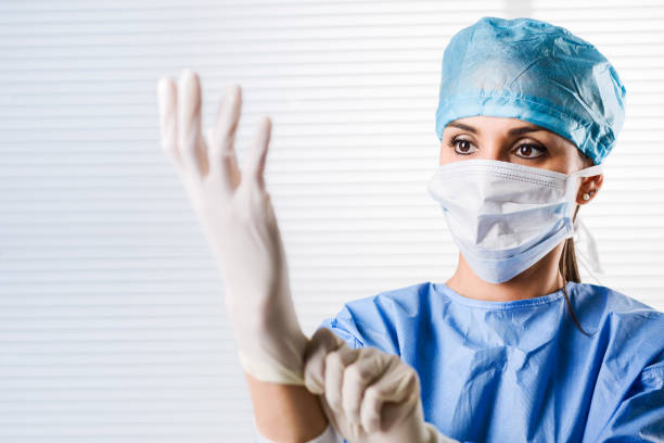 Female doctor Surgeon putting on surgical gloves stock photo