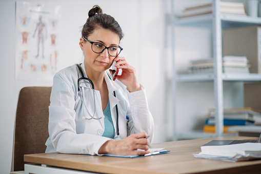 istock Female doctor taking a call from a patient during quarantine. Prescribing therapy from a remote medical office to isolated patient. 1220111090