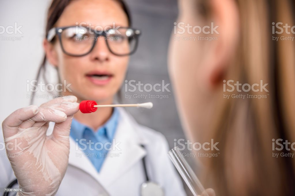 Female doctor taking a throat culture stock photo
