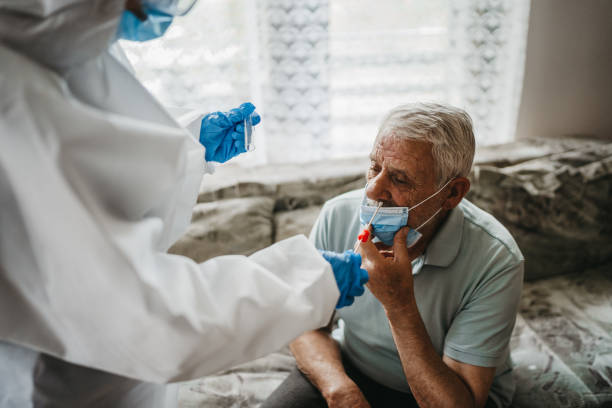 Female doctor taking nasal swab test from a senior man at home stock photo