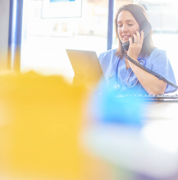 female doctor talking on the phone and using digital tablet at desk - nurse on phone stock photos and pictures
