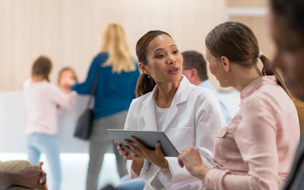 doctora hablando a paciente femenino - fila arreglo fotografías e imágenes de stock