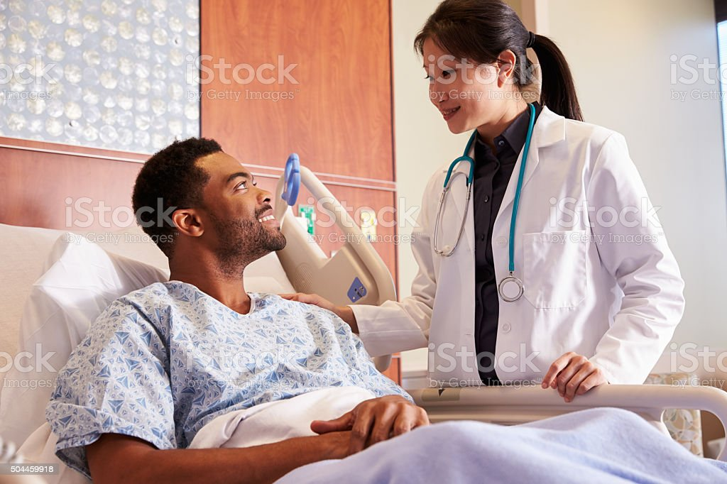 Female Doctor Talking To Male Patient In Hospital Bed stock photo
