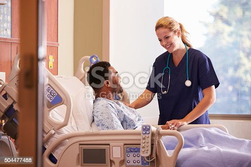 istock Female Doctor Talking To Male Patient In Hospital Bed 504477488