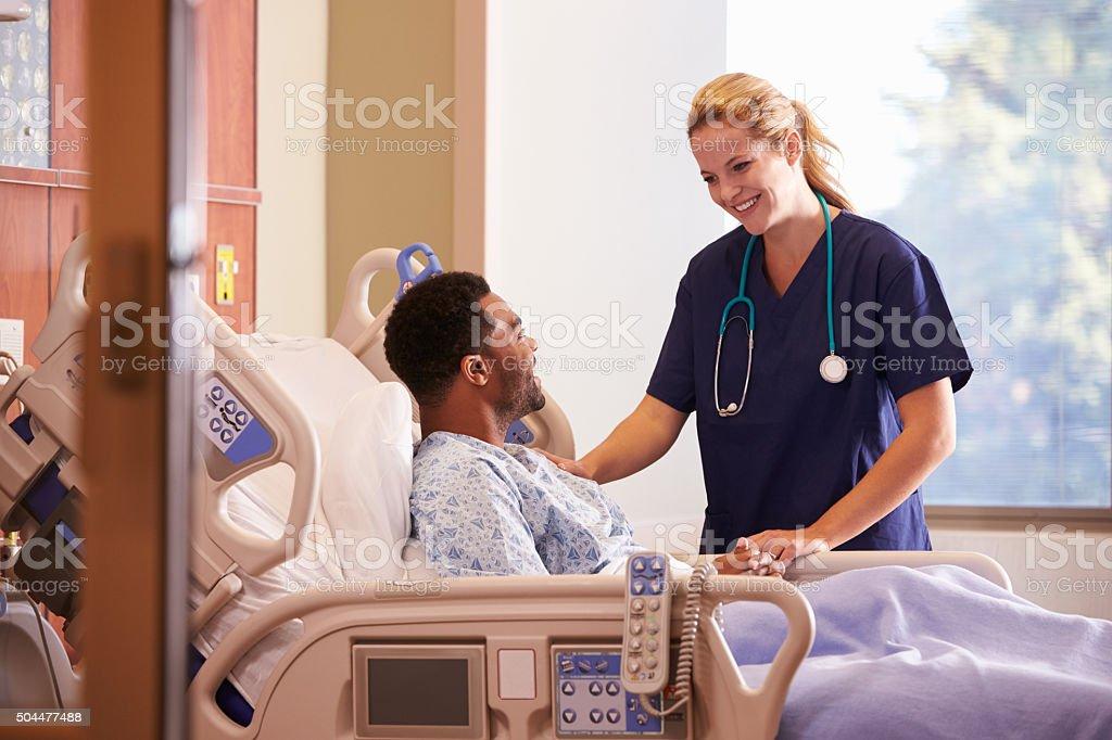 Doctora hablando al paciente de sexo masculino en Cama de Hospital - foto de stock
