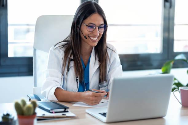 mujer doctora hablando con colegas a través de una videollamada con un ordenador portátil en la consulta. - telehealth fotografías e imágenes de stock