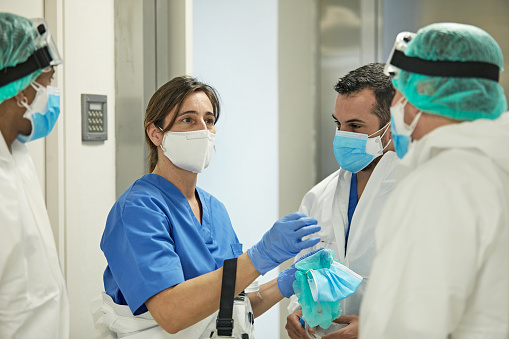 Mature Caucasian female medical professional standing with hospital coworkers dressed in varying degrees of protective wear.