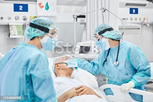 Female doctor talking with patient along coworker in ICU. Man is lying on bed amidst essential workers. Healthcare workers are in protective workwear.