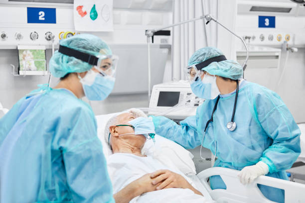 Female Doctor Talking With Patient Along Coworker Female doctor talking with patient along coworker in ICU. Man is lying on bed amidst essential workers. Healthcare workers are in protective workwear. life support machine stock pictures, royalty-free photos & images