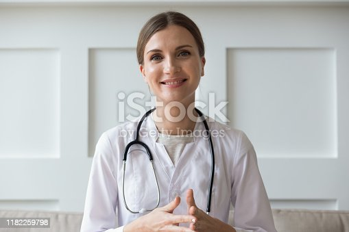 Head shot of woman wearing white coat stethoscope on shoulders looking at camera, doctor make video call interact through internet talk with patient provide help online counseling and therapy concept
