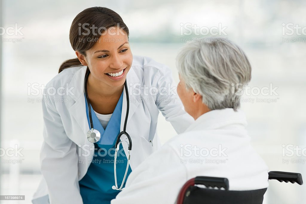 Female doctor talking with senior patient stock photo