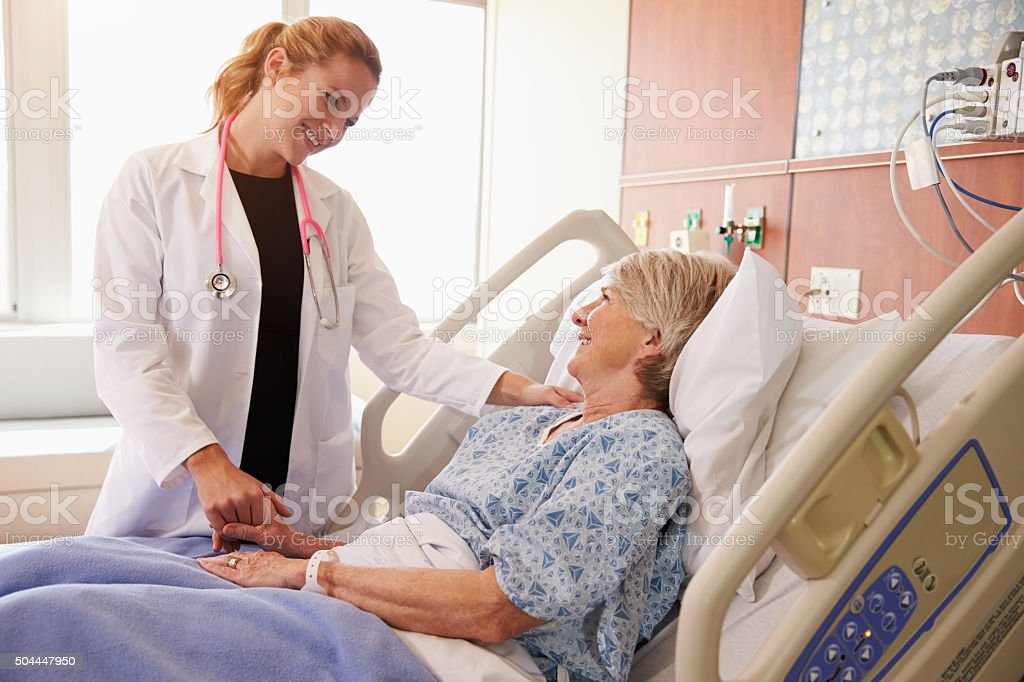 Female Doctor Talks To Senior Female Patient In Hospital Bed stock photo