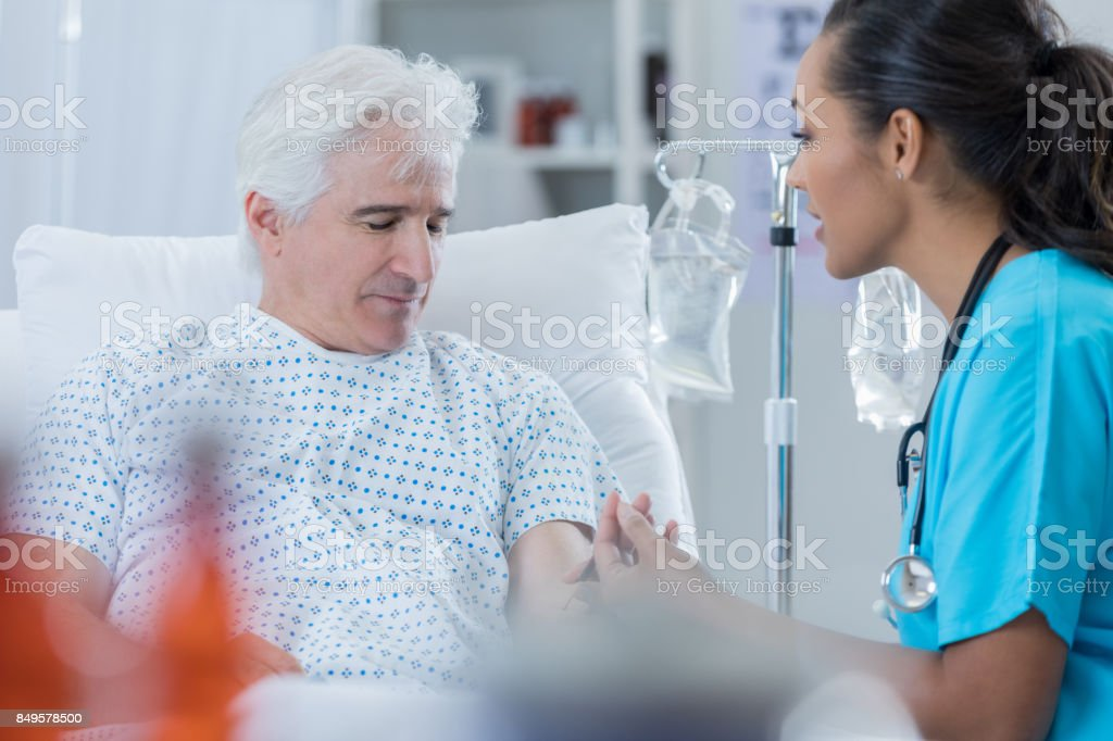 Female doctor talks with male patient stock photo