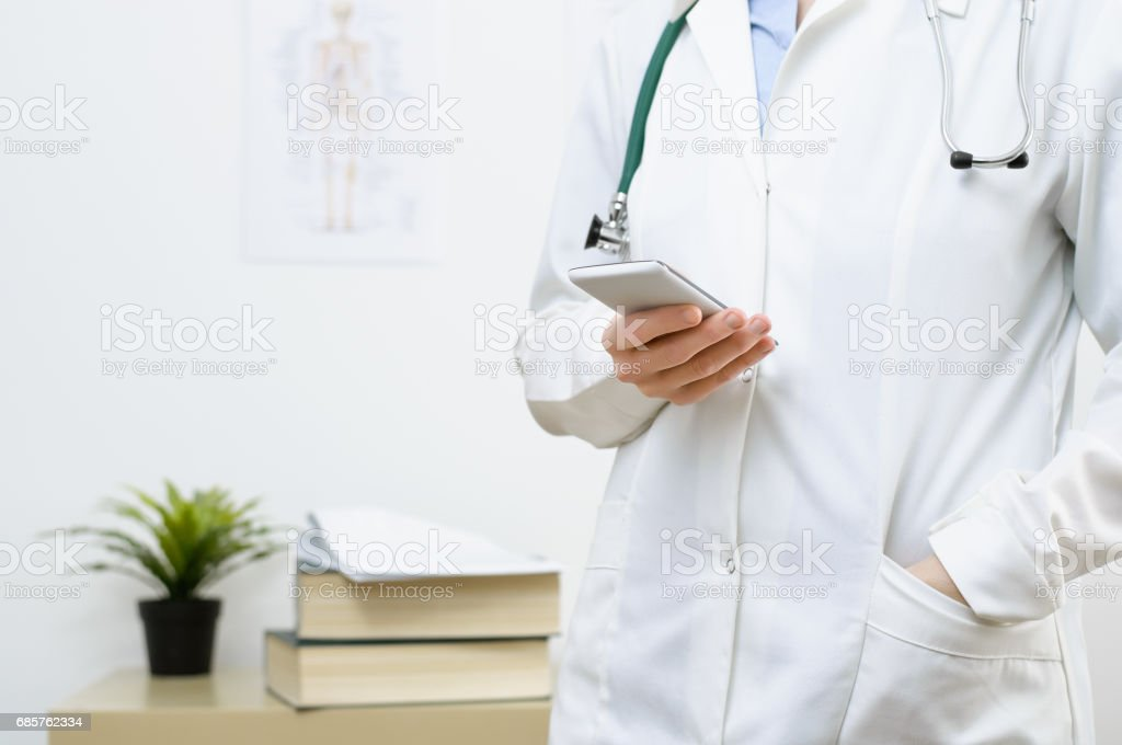 A female doctor texting on smartphone foto stock royalty-free
