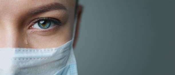 een vrouwelijke artstherapeut in een wit gewaad, masker en handschoenen. gezicht close-up. de dokter huilt en bidt. tranen in de ogen. pandemie en virusepidemie. coronavirus covid-19. kopieer ruimte. - tears corona stockfoto's en -beelden