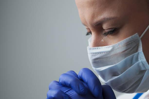 een vrouwelijke artstherapeut in een wit gewaad, masker en handschoenen. gezicht close-up. de dokter huilt en bidt. tranen in de ogen. pandemie en virusepidemie. coronavirus covid-19. - tears corona stockfoto's en -beelden