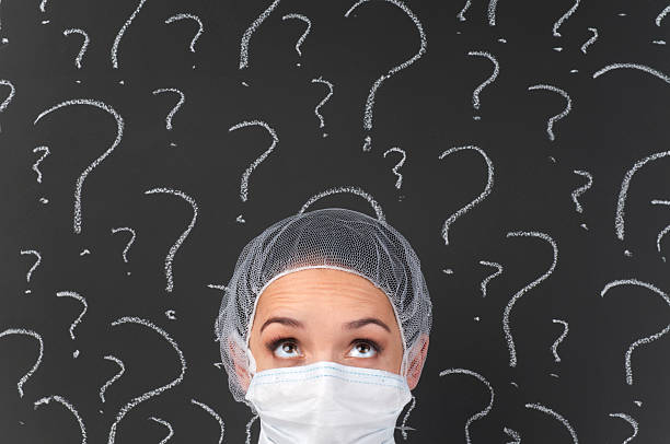 female doctor thinking in front of question marks - question mark asking doctor nurse stock photos and pictures