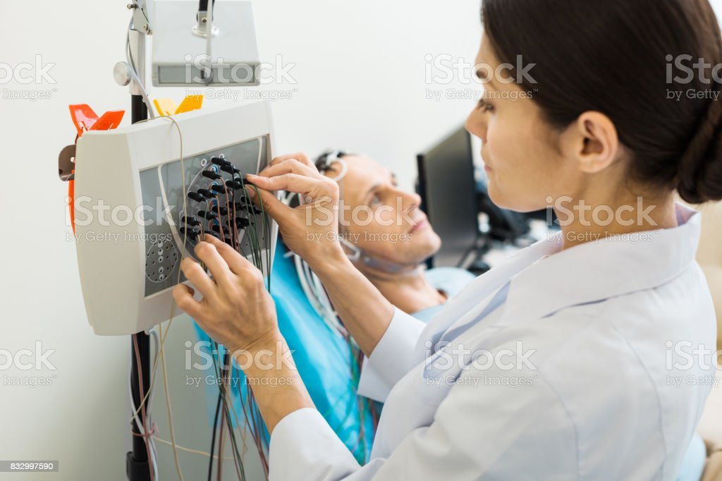 Female doctor tuning modern electroencephalograph stock photo