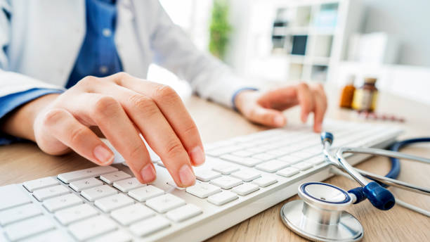 Female doctor typing on computer Female doctor typing on computer computer keyboard stock pictures, royalty-free photos & images