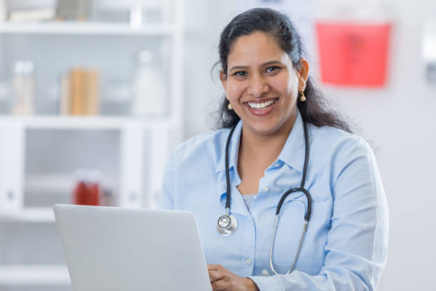 Female doctor uses laptop stock photo