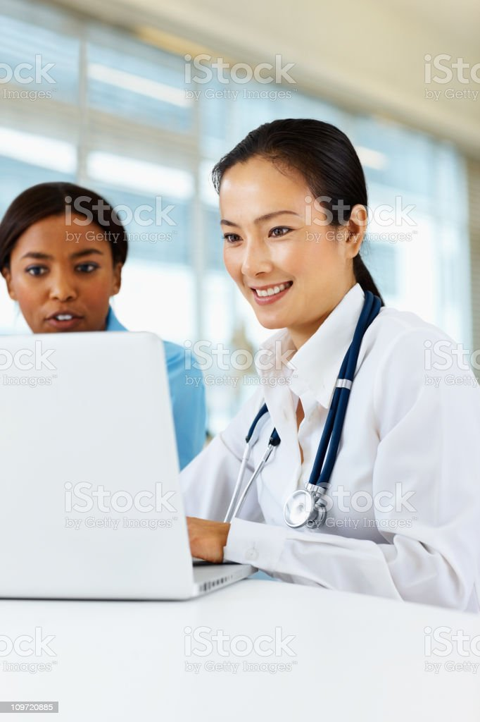 Female doctor using a laptop with colleague royalty-free stock photo