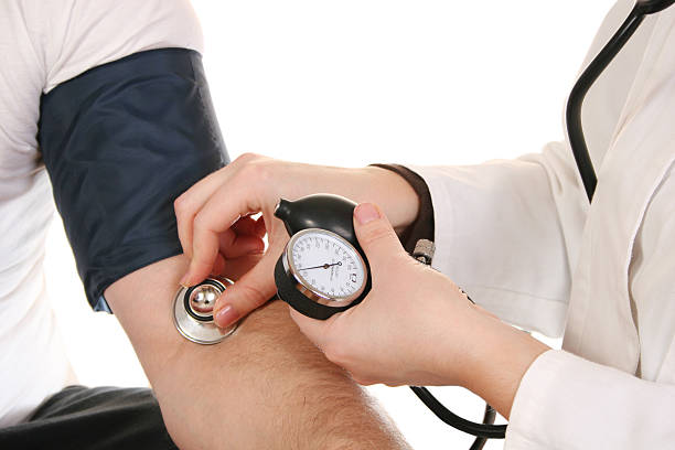 Female doctor using a stethoscope to check blood pressure stock photo