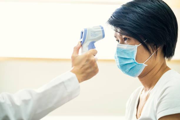 Ärztin mit Infrarot-Stirnthermometer im Krankenhaus – Foto