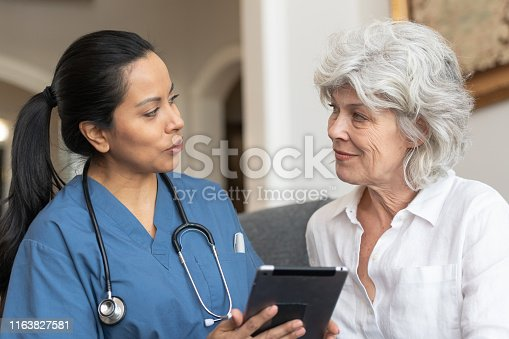 A female doctor of Latin descent consults a senior woman in a nursing home. The doctor is using a tablet to show her results from her most recent test.