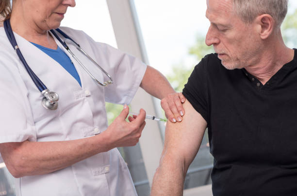 Female doctor vaccinating a man stock photo