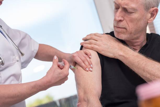남자에 우 두를 접종 하는 여성 의사 - flu shot 뉴스 사진 이미지